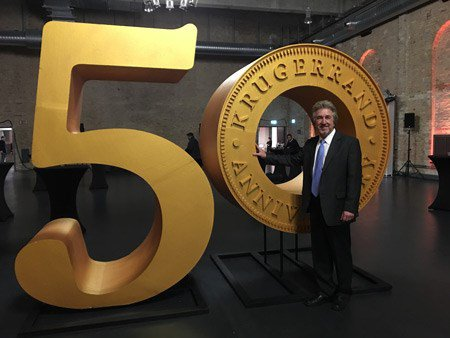 ANA President Jeff Garrett in front of giant Krugerrand 50th Anniversary display.