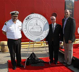 From left to right: Assistant Commissioner of the Canadian Coast Guard Wade E. Spurrell, Royal Canadian Mint Chair James B. Love and MP Jeff Watson (Essex) unveil a $20 fine silver collector coin celebrating 50 years of the Canadian Coast Guard at the Government Wharf in Sarnia, Ontario (July 13, 2012)