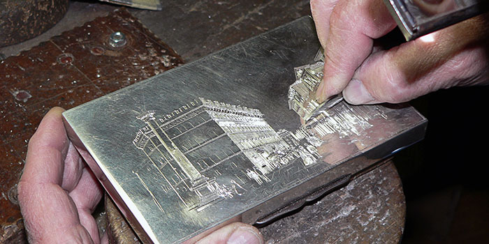 Silversmith engraves metal box