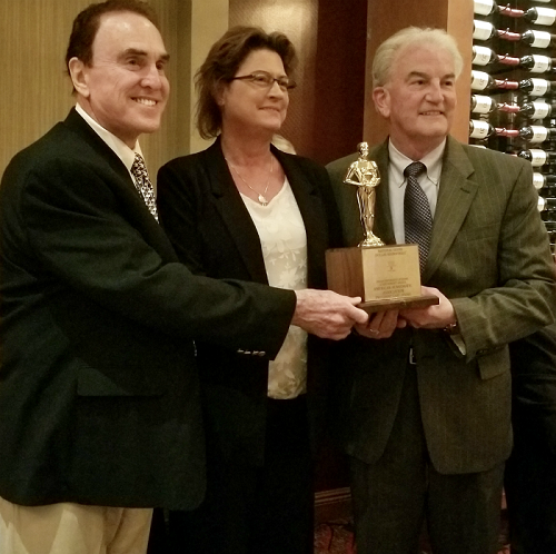 John Highfill (left) presents the NSDR Corporate Lifetime Achievement Award to American Numismatic Assocation Executive Director Kim Kiick and ANA President Gary Adkins.. Photo courtesy American Numismatic Association (ANA)