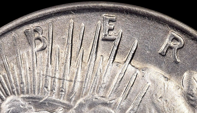 Detail, counterfeit 1928 Peace Dollar. Tool marks can be seen on the top of the obverse. Image courtesy NGC
