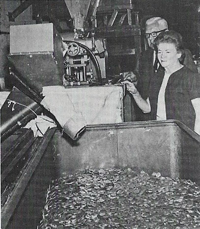 Eva Adams watches a coin sorting machine pull out silver coins. Image Credit: Coin World.